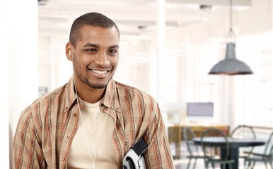 Happy young black man listening to music