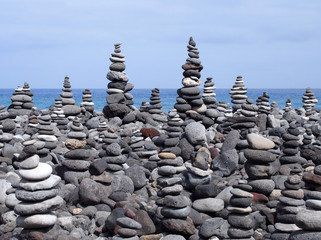 rock art piles and towers of grey stones and pebbles on a beach with blue sky and blue sky