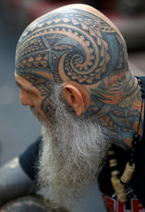A hand-tapping tattoo artist's own body art is seen on his head at the London Tattoo Convention, in London