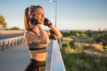 Young sporty woman with earphones listening to music during the sunset outdoors.