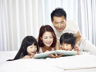 asian family with two children reading book in bed