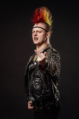 Portrait of punk rocker with Mohawk showing middle finger on a black background.