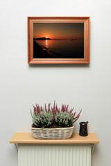 Dekoracja, wrzos w koszyku i obraz wschód, zachód słońca.
