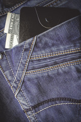 jeans. wallet with dollars in the back pocket. vertically