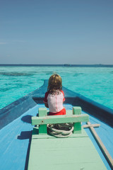 Little girl sailing in a boat in a tropical country