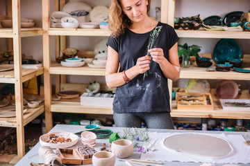 Ceramist using plants to print on a clay