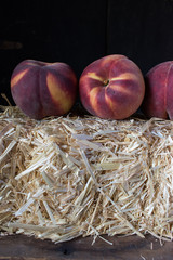 fall harvest of a group of ripe peaches on straw bale
