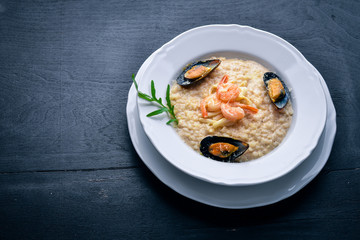 Risotto with seafood, shrimp, mussels and squids and cheese. On a wooden background. Top view. Free space.