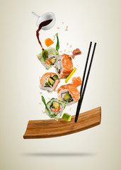 Flying sushi pieces served on wooden plate, separated on soft background