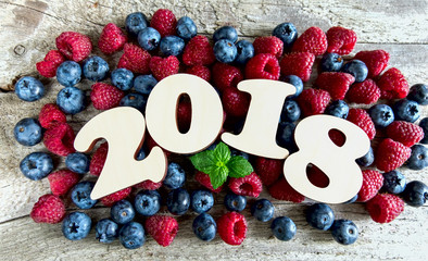 Year 2018 with blueberries and raspberries on a wooden background. Top view.