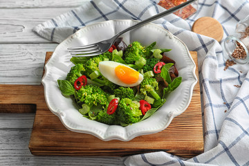 Dish with broccoli salad on wooden board