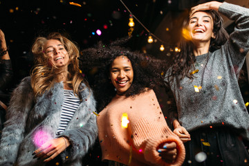 Group of female friends dancing, enjoying roof party with confetti