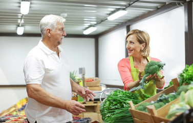 Mature shop assistant helping client choosing broccoli at market