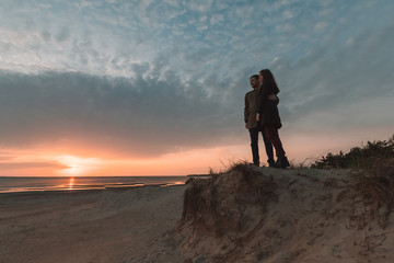 young loving couple watching the sunset at the sea in autumn.