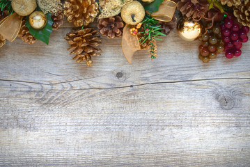 Christmas decorations with golden pine cones, apples and balls over a rustic wooden board.