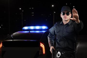 Policeman near car outdoors at night