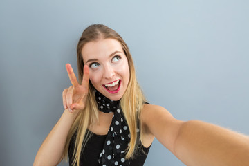 Young woman taking a selfie on a gray background