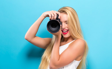 Young woman comparing professional camera on a solid background
