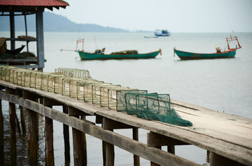 Fishing net on the planked footway and boats on the background