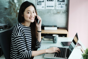 Young businesswoman talking smart phone while working at her office desk background, business people and communication concept, office lifestyle