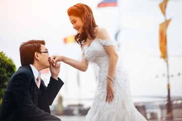 The bride and groom kissing on hand in river background. Asian wedding couple on outdoor background.