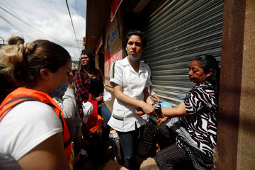 A student nurse attends to a woman after an earthquake, in Tecomatlan