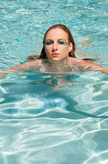 Red headed woman swimming in a pool.
