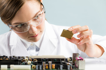 Electronics technology concept. Young woman engineer holding computer chip.