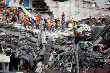 Members of rescue teams continue to search for people under the rubble of a collapsed building, after an earthquake, in Mexico City