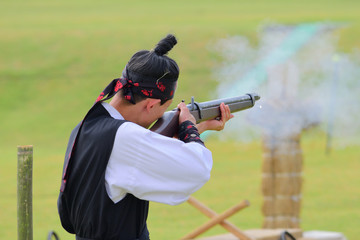 A gunman wearing a traditional korean dress and shooting a musket