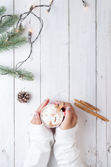 Christmas background - Girl hand holding cup of hot chocolate on white table with rustic decoration and copy space, flat lay, top view. vintage color tone style.