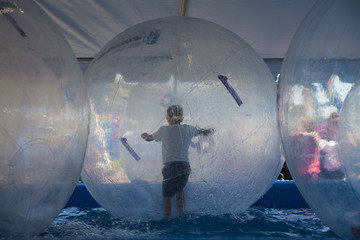 Wall Murals Ship Backside View of Young Boy Running in Human Sized Hamster Ball on Water