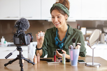 Beauty, cosmetics, e-commerce and blogging concept. Beautiful professional young female make up artist testing new facial cream or powder, recording video review on cosmetic products at home