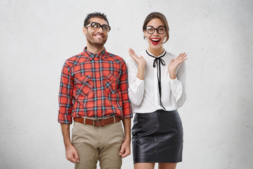 Funny clumsy nerdy unshaven guy wearing checkered shirt and eyeglasses with thick lenses looking at amazing fashionable female in weird way, falling in love with her. Love and relationships