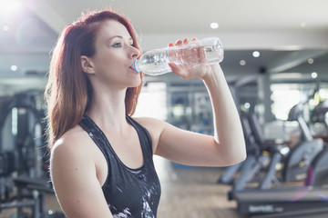 Young caucasian woman drinking water while doing exercise in gym. Health and fitness concept.