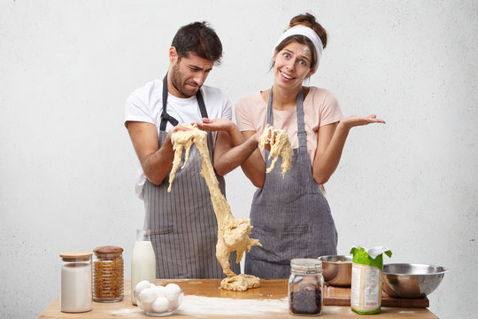 Kitchen disaster and bad cooking concept. Upset puzzled man keeps sticky dough, realizes that he spoiled everything and girlfriend tries to be optimistic, shrugs shoulders, encourages boyfriend