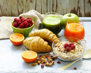 A healthy breakfast with croissants, fresh juice, nuts and raspberries