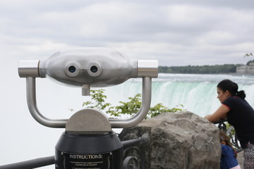 looking over Niagara Falls with a a telescope family