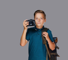 Preschooler boy taking pictures with a professional photo camera.