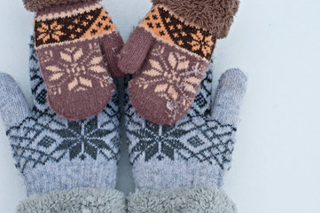 female hands in mittens are holding baby hands in mittens against the background of white snow