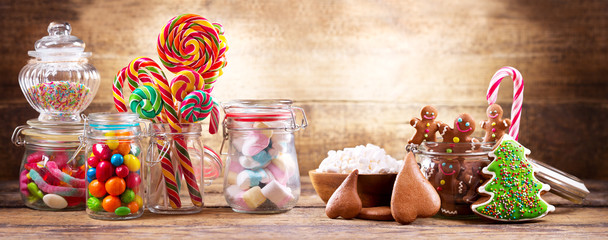Colorful candies, lollipops, marshmallows and gingerbread cookies  in a glass jars