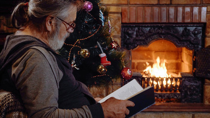 Senior man reading book near the fireplace and Christmas tree at xmas eve