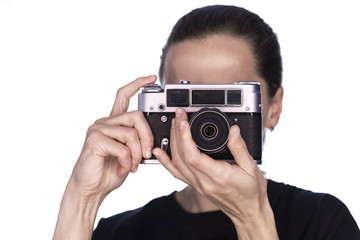 girl in black takes pictures on vintage camera on white background