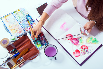 The dark-haired woman paints the pink flowers of peonies and wild rose with a wooden brush and watercolors in the drawing album, on the table lie a drawing bag, a leather case with brushes