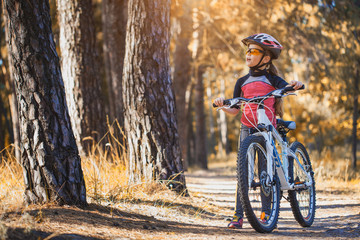 kid on a bicycle in the sunny forest. girl cycling outdoors in helmet