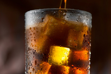 Cola pouring in glass with ice cubes over dark background