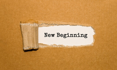 The text New Beginning appearing behind torn brown paper