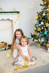 Christmas and new year 2018. Sisters are having fun and laughing by the fireplace and the Christmas tree