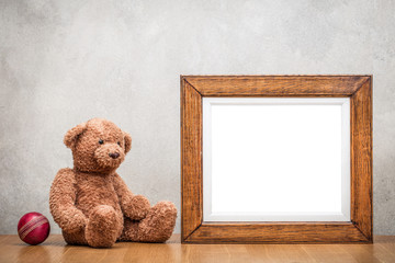 Retro oak wooden photo frame blank and Teddy Bear toy with leather ball front old textured concrete wall background. Vintage instagram style filtered photography