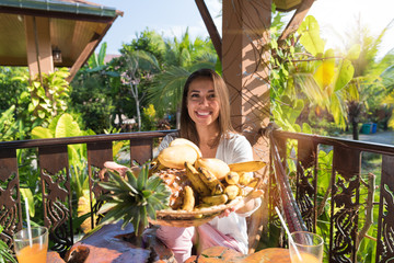 Beautiful Woman Hold Plate Of Delicious Fruits For Breakfast Happy Smiling Young Girl On Summer Terrace In Tropical Forest Healthy Food And Nutrition Concept